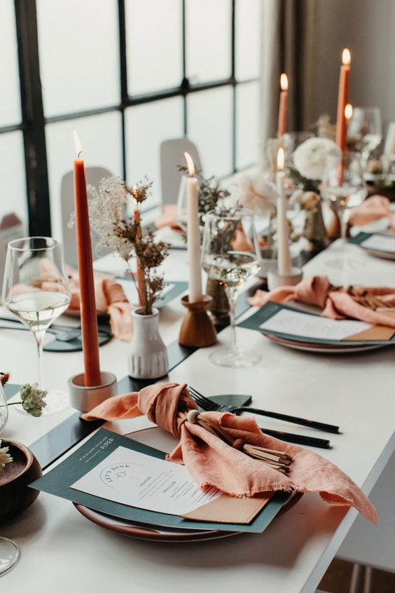 a serene modern wedding tablescape with a black runner, menus and cutlery, orange npakins and candles, cluster centerpieces and greenery