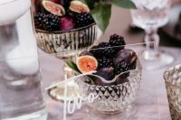 a sheer acrylic table number and crystal bowls with figs and blackberries for decadent fall table decor