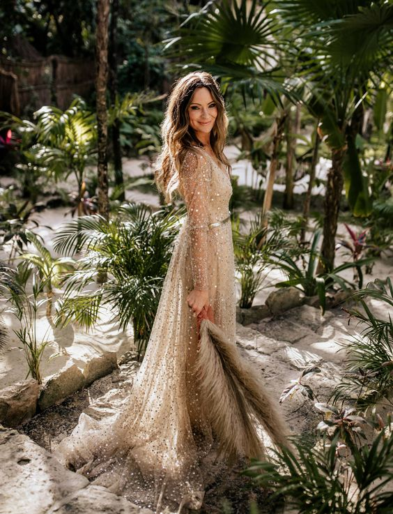 a sheer fully embellished A-line wedding dress with illusion sleeves and a train for a tropical elopement