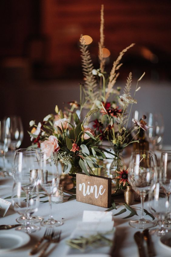a simple and relaxed fall wedding centerpiece with a cluster of vases, greenery, burgundya dn pink blooms and a wooden table number