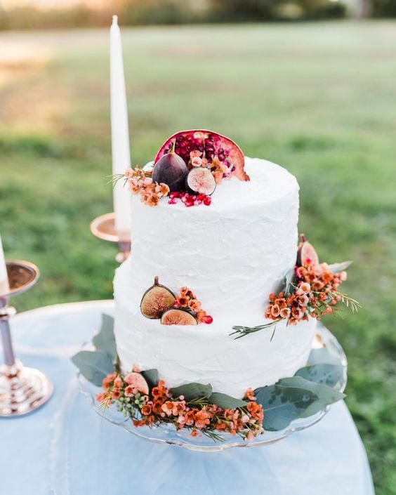 a simple and stylish fall wedding cake with bright blooms, pomegranates and figs is an idea that always works