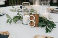 a simple fall centerpiece of candles in tall glasses, greenery and a wooden table number for a relaxed wedding