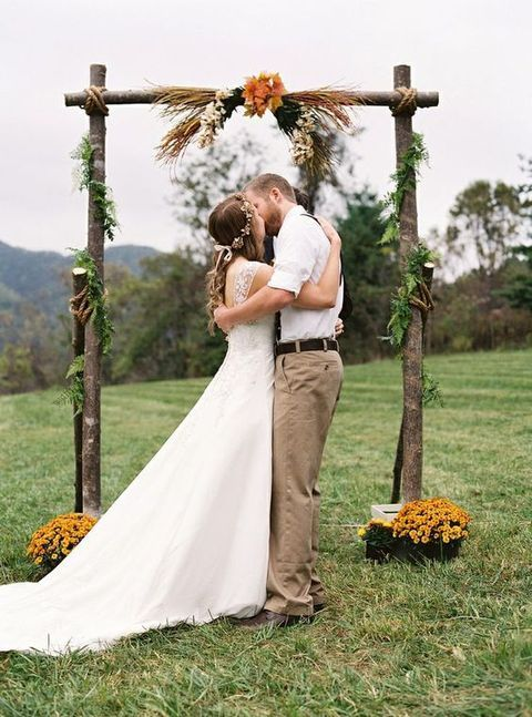 a simple outdoor fall wedding arch with grasses, leaves and blooms around for a backyard or rustic fall wedding