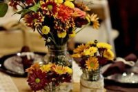 a simple rustic fall wedding centerpiece of a wood slice, fall blooms in jars with lace and twine
