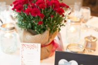 a simple rustic fall wedding centerpiece of deep red blooms wrapped with burlap and a burgundy ribbon