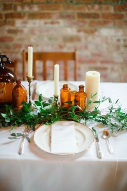 a simple tablescape with greenery, amber bottles, neutral candles and elegant cutlery and plates