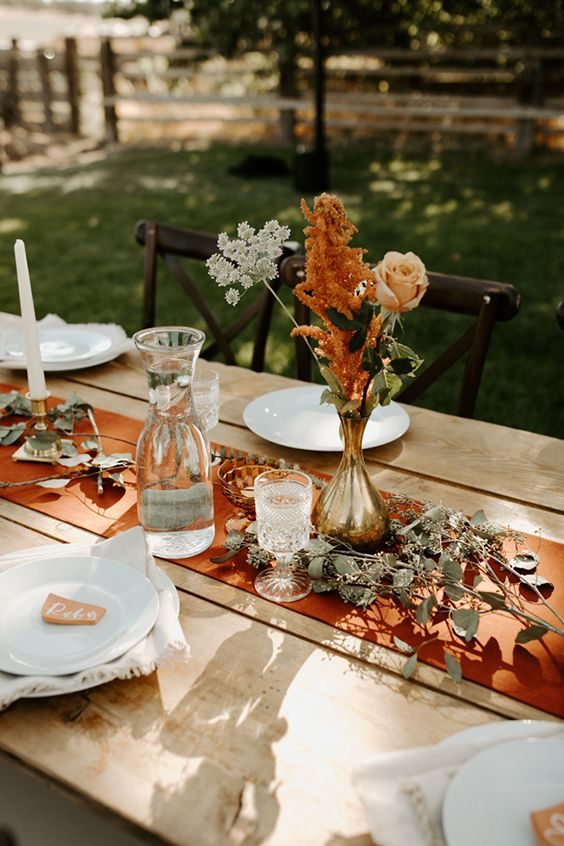 a simple yet chic fall wedding tablescape with a rust runner, rust blooms and cards, white porcelain and candles