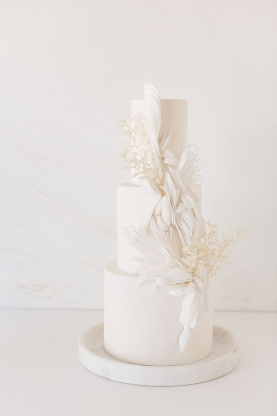 a sophisticated wedding cake with sugar feathers and white dried leaves is a refined dessert