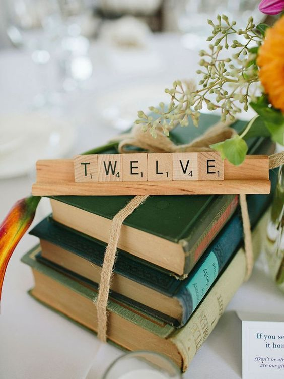 a stack of vintage books with a rope, a scrabble table number and some blooms for a lovely fall centerpiece