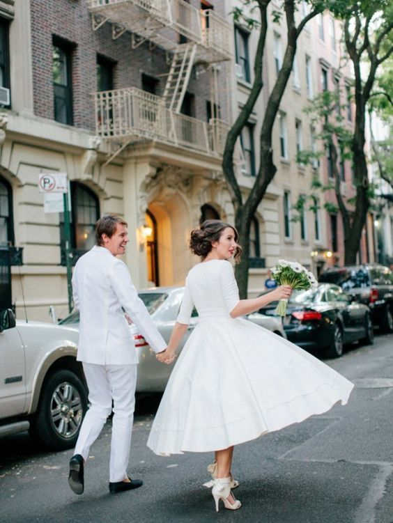 a statement tea length wedding dress with short sleeves and a full skirt, white strappy shoes and a red lip