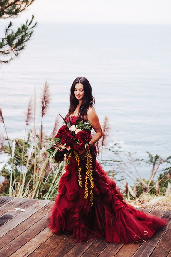 a strapless burgundy mermaid wedding dress with draperies and a cascading wedding bouquet with greenery and burgundy blooms