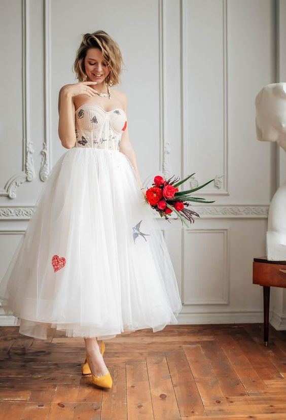 a strapless tea length wedding dress with a corset with butterflies, a bird and a heart, a tulle skirt, yellow shoes for a whimsical look