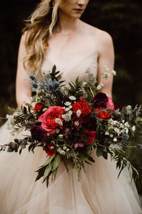 a stunning moody fall wedding bouquet of depe red, pink, purple and white blooms, greenery and thistles is a gorgeous idea for a moody wedding