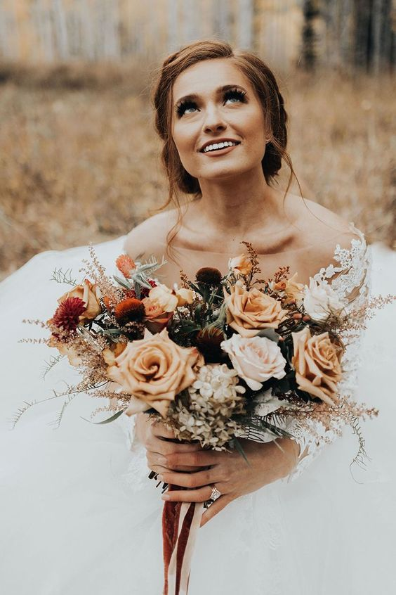 a stylish fall wedding bouquet of blush, rust, burgundy, deep purple, greenery, dried foliage and with long ribbons is cute and chic