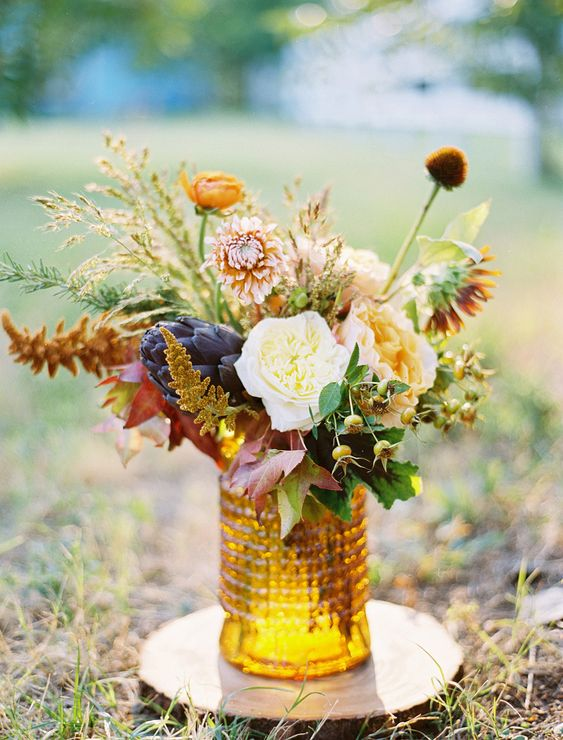 a stylish fall wedding centerpiece of an amber vase, white, blush and deep purple blooms and greenery