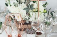 a stylish rustic centerpiece of a wooden crate with white blooms and greenery, dark succulents, a copper candleholder and a copper and white table number