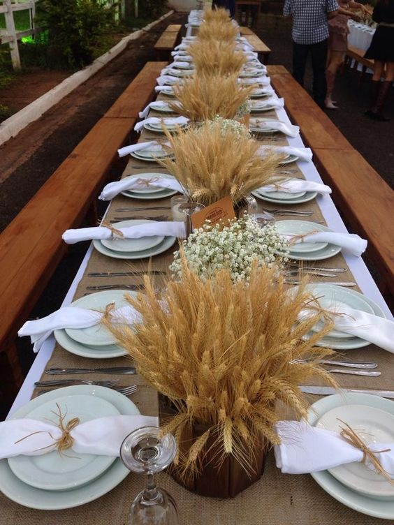 a stylish rustic wedding tablescape with wheat arrangements and baby's breath ones, a burlap tablecloth and green plates
