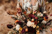 a super bold fall wedding bouquet of blush, yellow, orange and purple blooms, berries, greenery and soem grasses is a dimensional and textural idea
