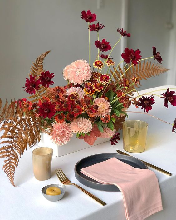 a super bright box wedding centerpiece with pink, rust and burgundy blooms, dried fern leaves looks spectacular