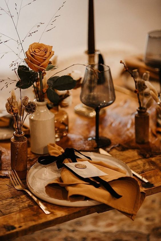 a super chic wedding tablescape with amber blooms and napkins, porcelain vases and dried herbs and some grasses