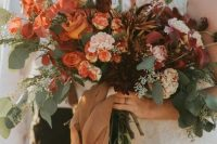 a super lush fall wedding bouquet of rust, blush, orange, burgundy blooms, lots of greenery and bright foliage, long tan ribbons is wow