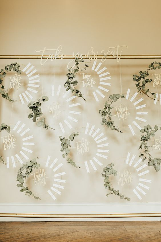 a super stylish seating chart of embroidery hoops with eucalyptus and paper tags is amazing for a modern wedding
