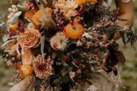 a super textural and dimensional fall wedding bouquet of yellow, pink, deep purple and burgundy blooms, twigs, greneeyr and grasses is amazing