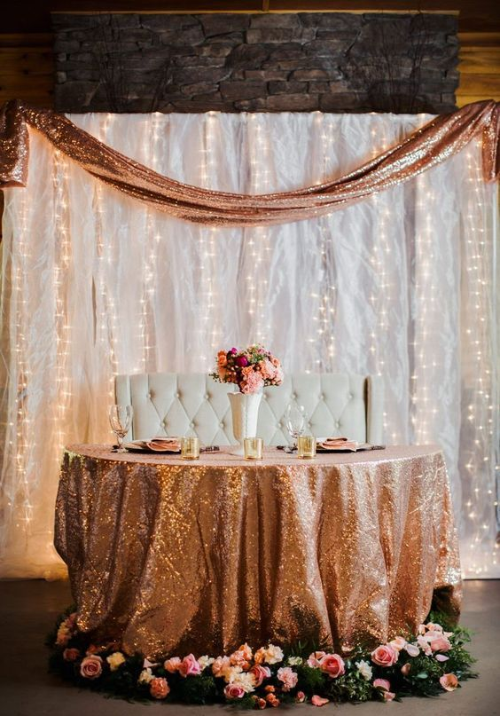 a sweetheat table covered with a copper sequin tablecloth and a copper sequin runner in the backdrop