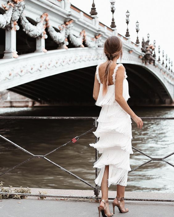 a tea length fringe wedding dress with straps and a cutout back, with copper shoes for a modern wedding look