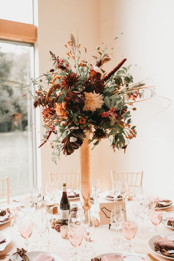 a textural tall floral centerpiece in a copper vase, with lots of various greenery, rust and burgundy blooms and dark foliage