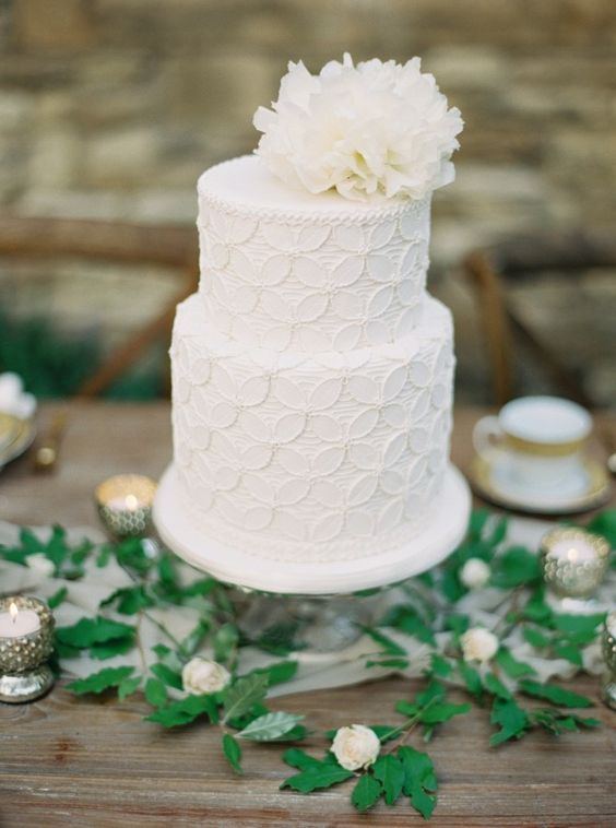 a textural white wedding cake with a floral pattern and a white white bloom on top looks vintage-like and chic