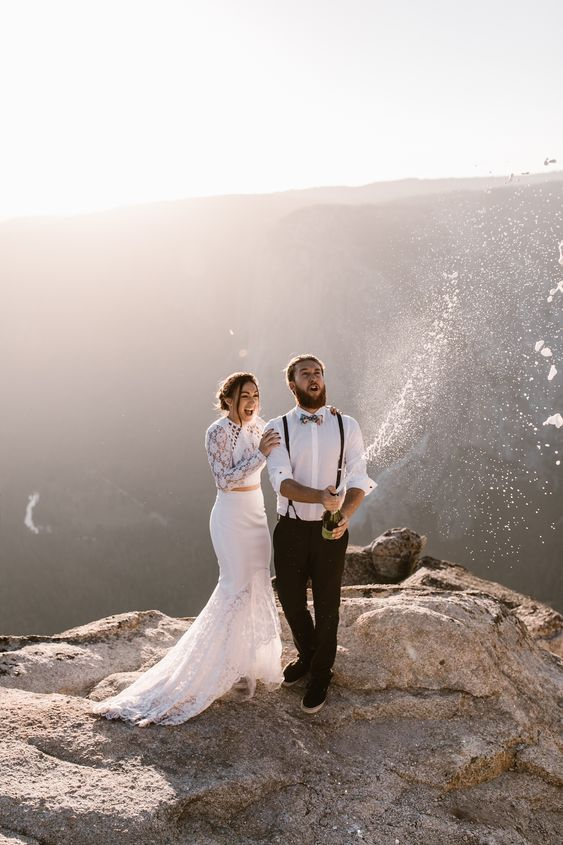 a two piece wedding dress of lace with a crop top with long sleeves and a mermaid skirt with train