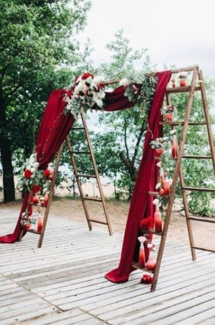 a unique wedding arch made of ladders, with a burgundy curtain, greenery, blooms and ombre red vases