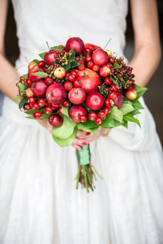 a unique wedding bouquet of fresh red and burgundy fruits and foliage is amazing for the fall