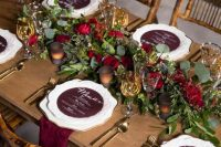 a very elegant and refined rustic fall wedding tablescape with a greenery and red rose runner, candles, burgundy menus and napkins plus gold cutlery