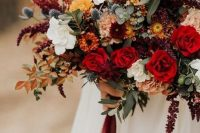 a vibrant fall wedding bouquet of deep red, white, burgundy, rust blooms, greenery, bold fall foliage and thistles is amazing