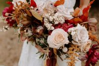 a vibrant fall wedding bouquet of fuchsia, blush, rust blooms, berries, dark foliage and matching ribbons is great for a boho wedding