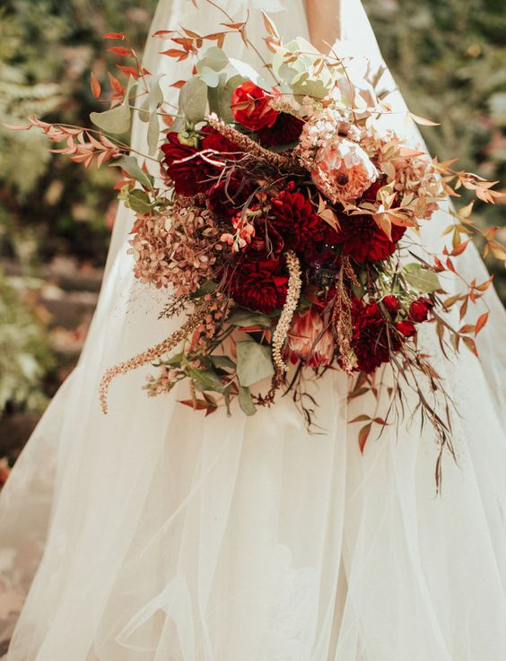 a vibrant fall wedding bouquet of pink and burgundy blooms, greenery and bold fall foliage, grasses and dried blooms is amazing