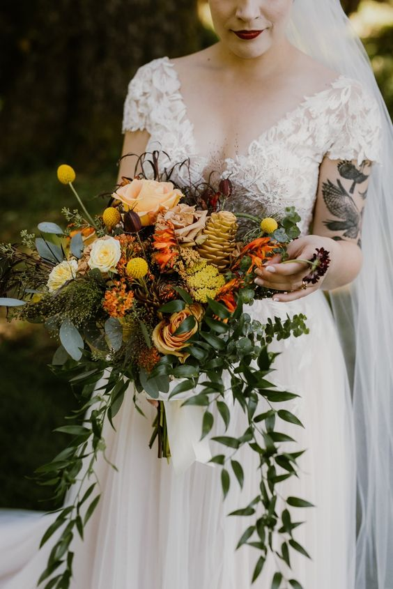 a vibrant fall wedding bouquet of pink, yellow, orange blooms, greenery, billy balls and even a yellow pinecone with cascading touches