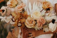 a warm-colored fall wedding bouquet of yellow, neutral and rust blooms, pink touches, grasses, fronds for a boho fall wedding with a warm color palette
