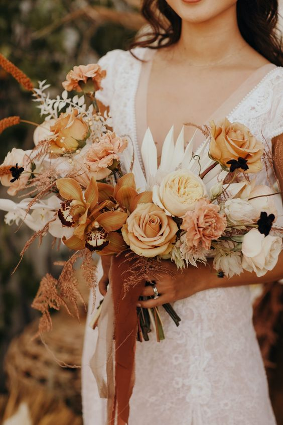 a warm colored fall wedding bouquet of yellow, neutral and rust blooms, pink touches, grasses, fronds for a boho fall wedding with a warm color palette