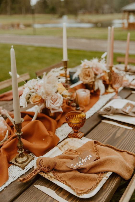 a warm-colored wedding tablescape with a rust table runner, antlers, neutral blooms and candles, rust napkins and amber glasses