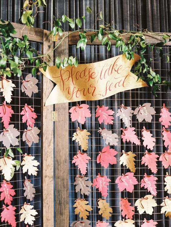 a wedding seating chart of bright paper leaves, greenery and a banner is a nice idea for a fall wedding that you can DIY