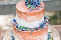 a white and copper brushstroke wedding cake with greenery, berries and thistles is very bold