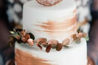 a white and copper wedding cake with copper leaves, a wire ball and copper brushstrokes is very bold