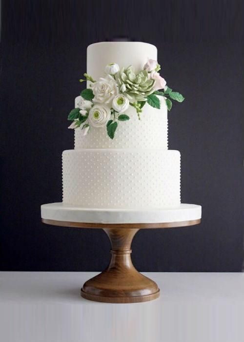 a white and polka dot wedding cake decorated with sugar blooms and leaves is a lovely wedding dessert