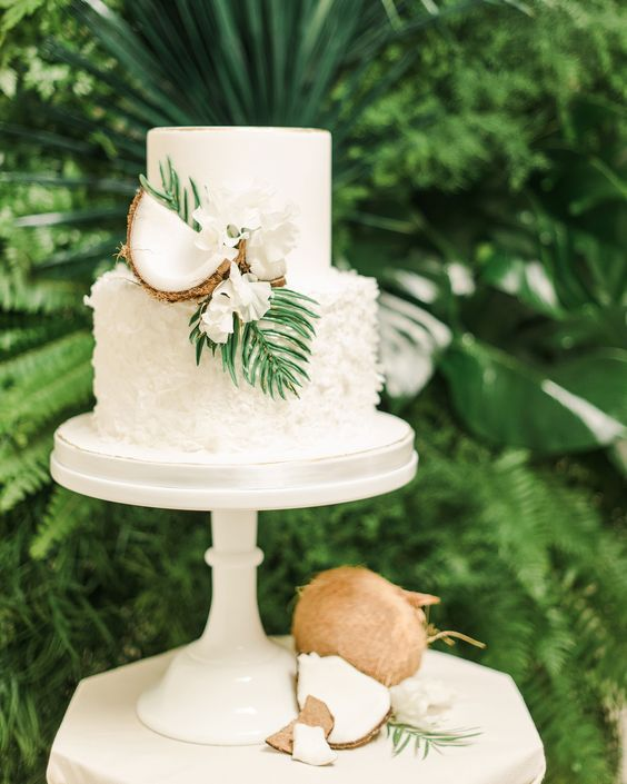 a white plain and textural wedding cake decorated with white blooms, greenery and coconuts for a tropical wedding