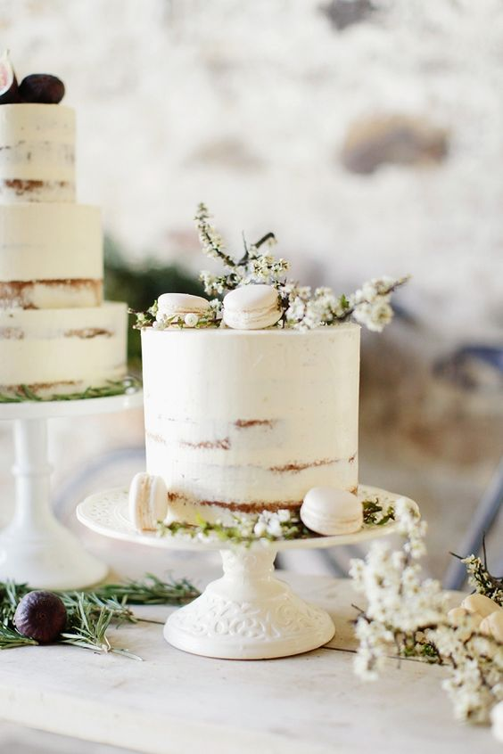 a white semi-naked wedding cake topped with blooms and white macarons is a gorgeous idea for a spring wedding