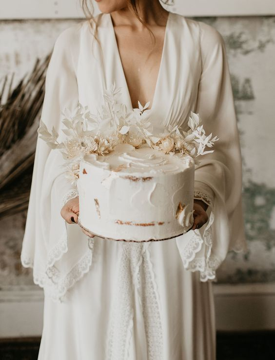 a white semi-naked wedding cake topped with white dried blooms and leaves for a boho wedding
