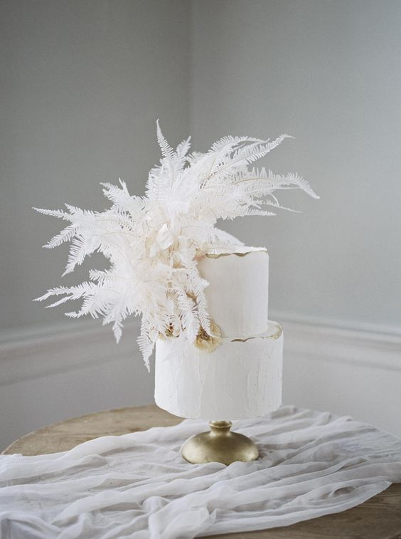 a white textural wedding cake with a gold ege and lush white dried leaves is a cool wedding dessert